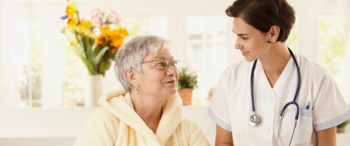 Ζεστή στιγμή φροντίδας μεταξύ γυναίκας γιατρού και όμορφης ηλικιωμένης, όπου κοιτάζονται στα μάτια χαμογελώντας